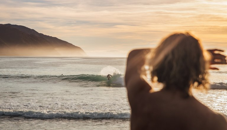 Someone watching surfers riding waves in the sunset