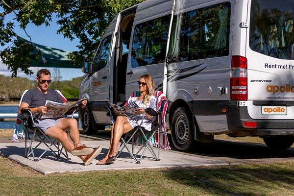 Couple in camping chairs sitting next to Apollo Euro Tourer
